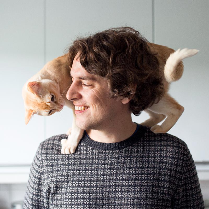 Mies kotioloissa lemmikkikissa hartioillaan. En man i hemmiljö med en katt på axlarna.