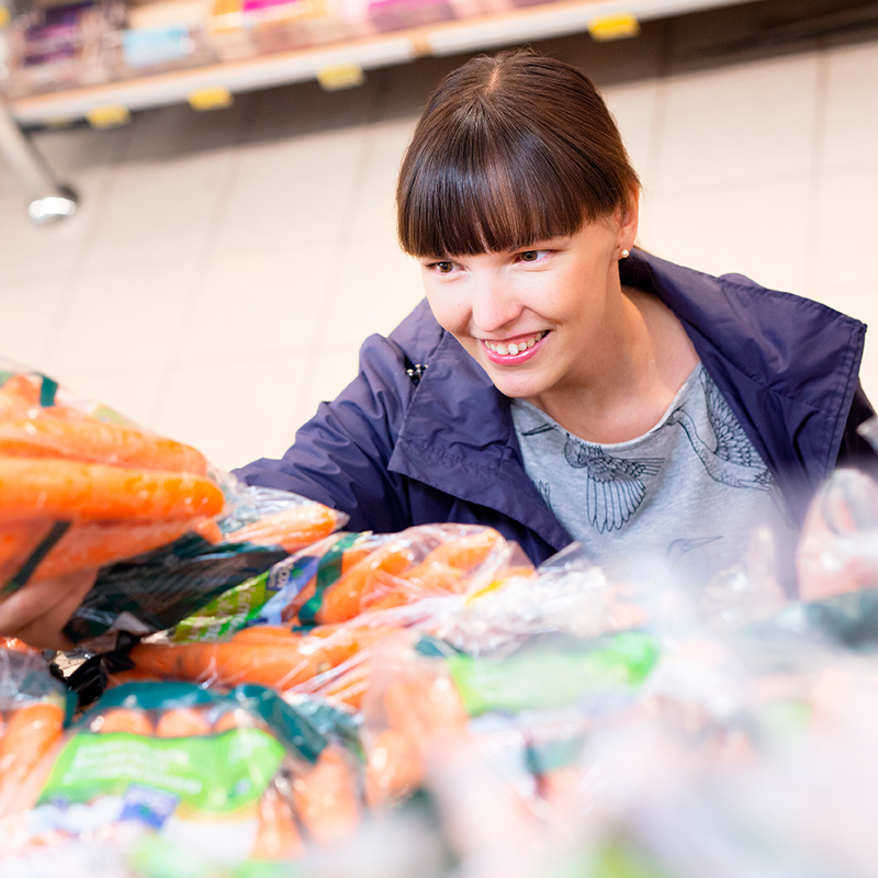 Nainen valitsee ruokakaupassa porkkanapussin. En kvinna väljer en påse morötter i mataffären.
