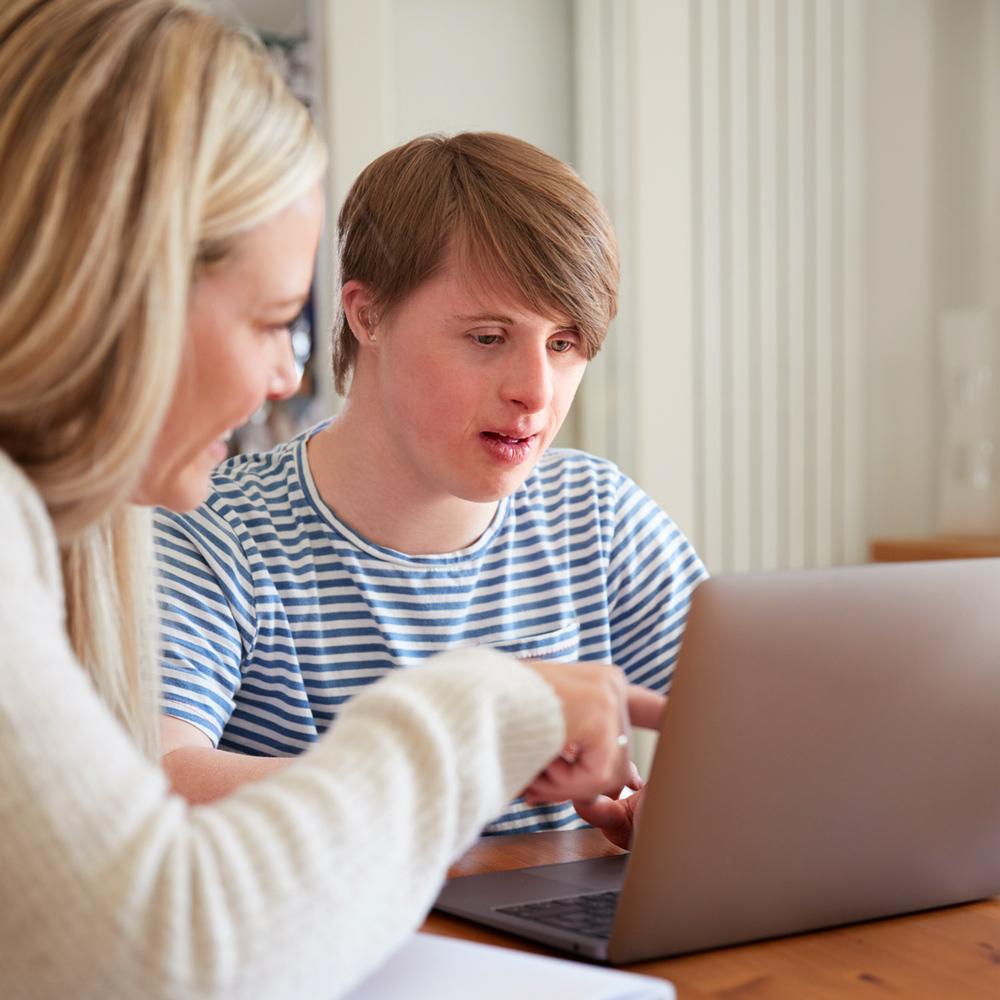 Aikuinen ja nuori henkilö, jolla on Downin syndrooma istuvat tietokoneella.