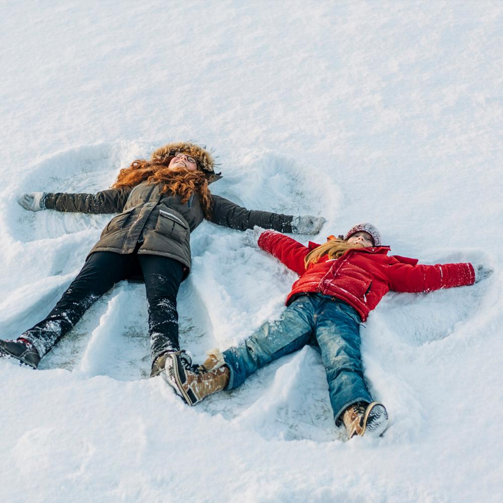 Kaksi alakouluikäistä lasta makaa lumessa selällään ja tekee lumienkeleitä.