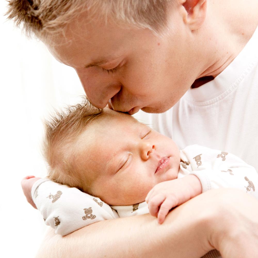 Personen kysser barnet i pannan.