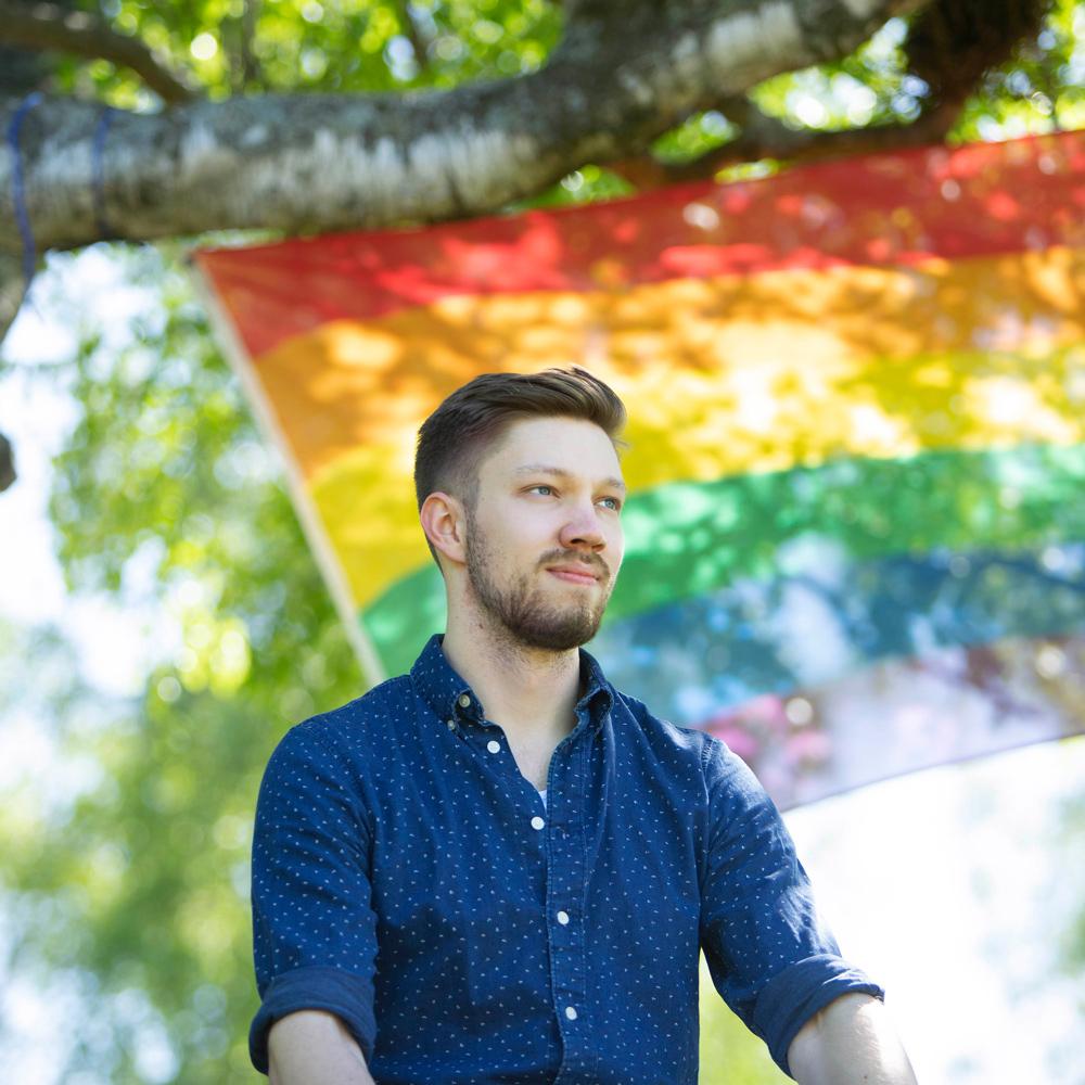 En person framför en regnbågsflagga.