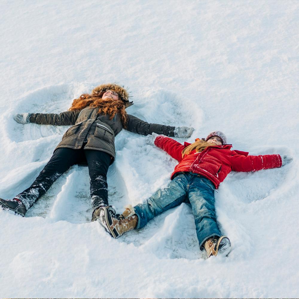 Två barn i lågstadieåldern ligger på rygg i snön och gör snöänglar.